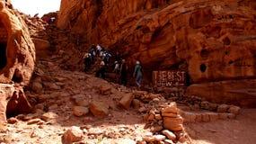 Petra, Jordanië 19 04 2014: Toeristentrekking omhoog de berg met beste meningsteken in worldwonder in Petra in Jordanië Stock Foto