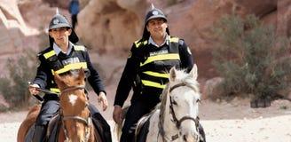 Petra Wadi Musa, Jordanien, mars 9 2018: Två poliser på hästrygg med roliga finnehuvar och signalvästar som skyddar många I arkivbilder