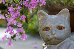 Petrified cat. Sphinx-like garden picture with flowers Stock Photography