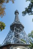 Petrin Lookout Tower on top of hill overlooking city. Petrin Lookout Tower framed by trees on top of hill overlooking city of Prague, Czech Republic Stock Photos