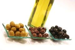 Petróleo verde-oliva do ouro no buttle com azeitonas sobre o branco Imagem de Stock Royalty Free