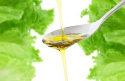 Petróleo verde-oliva que está sendo derramado em uma colher Foto de Stock