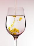 Petróleo verde-oliva que está sendo derramado no vidro de vinho Imagem de Stock