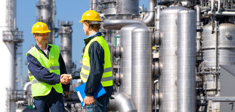 Petrochemical contractors. Two petrochemical contractors closing a deal in front of an oil refinary Royalty Free Stock Photo