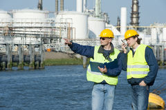 Petrochemical Engineers. Two petrochemical engineers discussing a project outdoors Stock Photo