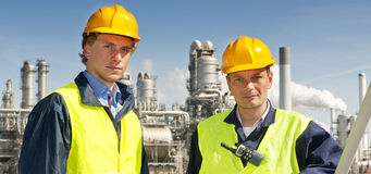 Petrochemical engineers. Two petrochemical engineers in front of a refinery, wearing hard hats and safety vests Stock Photos