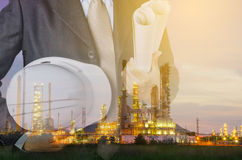 Petrochemical industrial estate concept. Engineering man and safety helmet standing against oil refinery plant in heavy petrochemical industrial estate Royalty Free Stock Photo