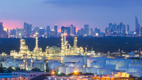 Petrochemical industrial refinery with city background after sunset Royalty Free Stock Photos
