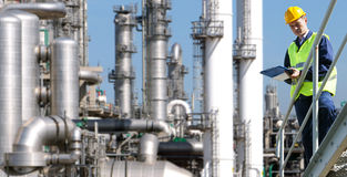 Petrochemical industry. A petrochemical engineer, with a noteboard in his hand in front of a huge refinery Stock Photos