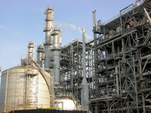 Petrochemical Plant. A petrochemical unit in operation with columns, tanks, flares and piping against a blue sky Stock Image