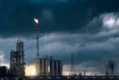 Petrochemical Plant And Fire On Flare Stack While Burning Toxic  Oil And Gas With Cloudy Stock Photos