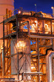 Petrochemical Plant at Night. A petrochemical unit in operation with columns, tanks, and piping against a blue evening sky Stock Photos