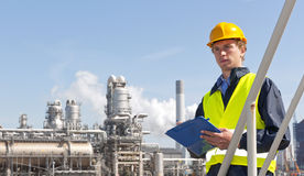 Petrochemical supervisor. Young supervisor with a note board and pen in his hands, wearing a hard hat and safety vest in front of a petrochemical plant and Stock Photo