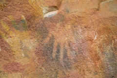 Petroglyph. Cave of Hands Petroglyph in Argentina, cueva de las manos. Handprints made with red, yellow and black colour paint of ancient people on the wall of a Stock Photo