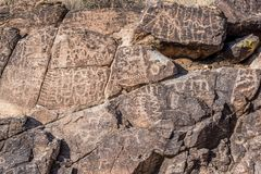 Petroglyphs etched in rocks in Arizona. Petroglyphs etched in brown rocks in the desert in Arizona on a sunny day Royalty Free Stock Image