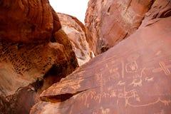 Petroglyphs na rocha vermelha imagem de stock