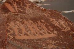 Petroglyphs sned in i stenen i Peru Arkivfoto
