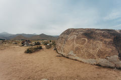 Petroglyphs on stones. In are far mountains are visible Stock Image