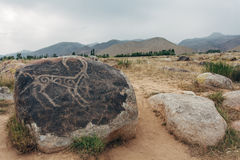 Petroglyphs on stones. In are far mountains are visible Royalty Free Stock Photo