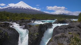 Petrohue waterfalls. With the Osorno and Calvuco volcanoes stock video footage