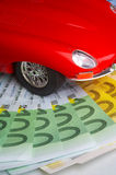 Petrol. Model of a car lying on the circle of money Stock Images