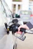 Petrol being pumped into a motor vehicle car. Petrol or gasoline being pumped into a motor vehicle car. Closeup of man pumping gasoline fuel in car at gas stock photo