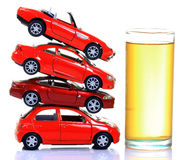 Petrol and cars. Glass full of petrol with heap of cars  isolated on white background Stock Photo
