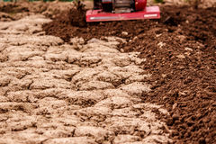 Petrol cultivator tills compacted soil. Red Petrol cultivator tills compacted soil Stock Photography