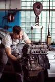 Petrol engine check up. Picture showing mechanic examining hanging car motor Stock Image