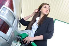 Petrol filling station. Business woman on filling station, while filling your car Royalty Free Stock Image