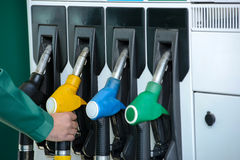Petrol filling station. Close-up of a men's hand using a fuel nozzle at a gas station. Petrol station. Filling station. Petrol. Gasoline Stock Images
