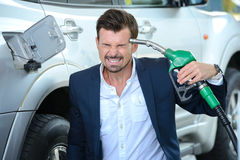 Petrol filling station. Emotional businessman shooting himself over crazy petrol prices Royalty Free Stock Photo