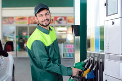 Petrol filling station. Smiling worker at the gas station, while filling a car Royalty Free Stock Photos