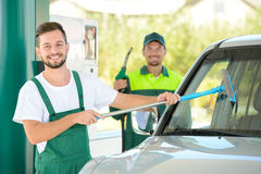 Petrol filling station. Washing car window while filling petrol cars at gas station Stock Photos