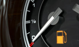 Petrol Gage Empty. A 3D render of an extreme closeup of a gas gage showing the needle at empty with an illuminated light indicating so Stock Images