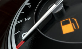 Petrol Gage Empty. A 3D render of an extreme closeup of a gas gage showing the needle at empty with an illuminated light indicating so Royalty Free Stock Photo