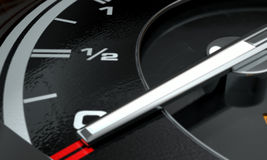Petrol Gage Empty. A 3D render of an extreme closeup of a gas gage showing the needle at empty with an illuminated light indicating so Stock Photos