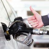 Petrol or gasoline being pumped into a motor vehicle car. Closeup of man, showing thumb up gesture, pumping gasoline. Petrol or gasoline being pumped into a royalty free stock photo
