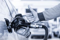 Petrol or gasoline being pumped into a motor vehicle car. Closeup of man, showing thumb up gesture, pumping gasoline. Petrol or gasoline being pumped into a stock photography