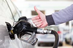 Petrol or gasoline being pumped into a motor vehicle car. Closeup of man, showing thumb up gesture, pumping gasoline. Petrol or gasoline being pumped into a stock images