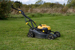 Petrol lawn mower. Yellow lawn mower on the green field Royalty Free Stock Photo
