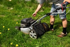 Starting an lawn mower to mow lawns. royalty free stock photography