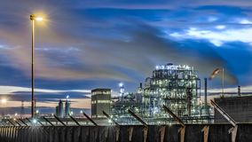 Petrol oil industry in italy at sunset. Beautiful sunset on a industrial site of petrol oil in north Italy under a cloudy blue sky with wind smoke and street stock photography
