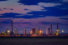 Petrol oil refinery located near a cultivated field at dusk. Petrol oil refinery producing fuel located near a cultivated field at dusk with some clouds in the royalty free stock photo