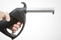 Petrol pump. Man's hand holding a petrol pump with a drip hanging from the end of the nozzle Stock Photography