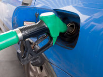 Petrol pump nozzle. Is filling up blue car royalty free stock photos