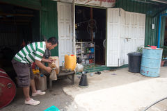 Petrol Refill Stop in Myanmar. FALAM, MYANMAR - JUNE 17 2015: Refilling petrol in the recently opened to foreigners area of Chin State - western Myanmar (Burma Royalty Free Stock Photo