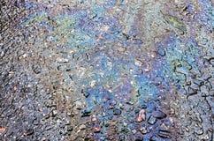 Petrol spill on asphalt road. Background texture stock images