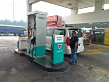 Petrol station. Man refuelling a car at a petrol station in Peninsular Malaysia stock photo