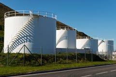 Petrol Tanks. White petrol tanks against blue sky royalty free stock photos